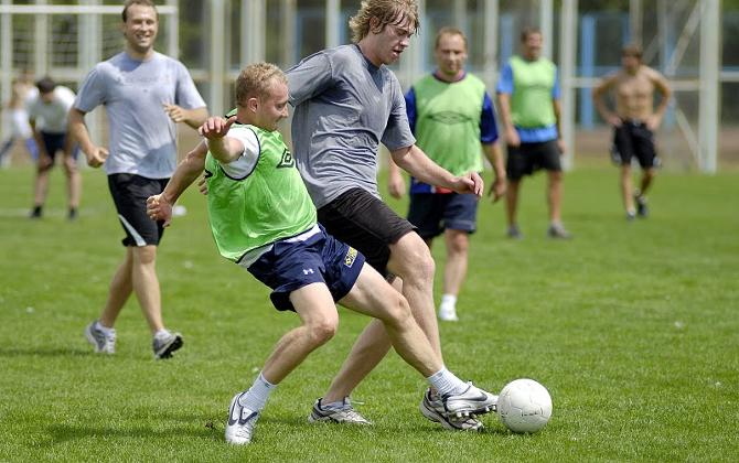 Начальник команды Артур Рекшта пытается забрать мяч у Сергея Шелега