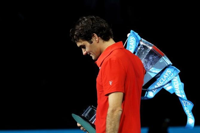 Роджер Федерер уносит с корта очередной трофей.